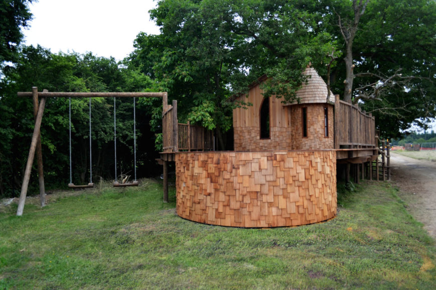 At the rear of the property, we can see the attached natural wood swing set standing to the left of the large fire pit space.