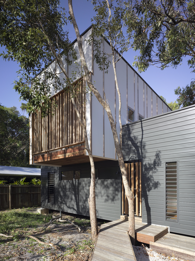 Windows and door on the front of the home are covered in thin wooden slats for privacy and shade, while the tall windows on the first floor are comprised of louvered segments for fresh airflow.