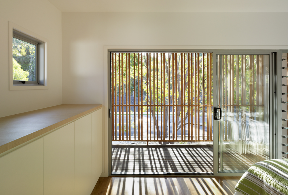 The master bedroom opens through full height sliding glass to this semi-private balcony, with natural wood slats casting staggered shadows across the space.