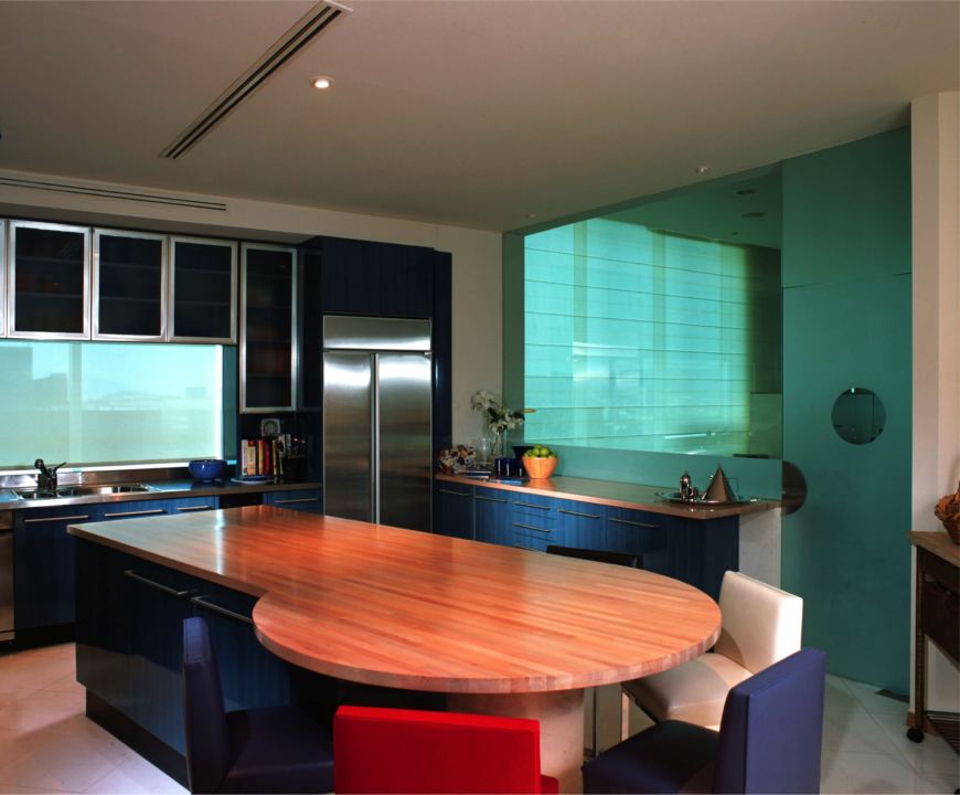 The glass-enclosed kitchen has a peek-through to the main living area. The kitchen island extends into a circular bar area with purple, red, and white seating around it. The metallic blue cabinets add another color into the mix.