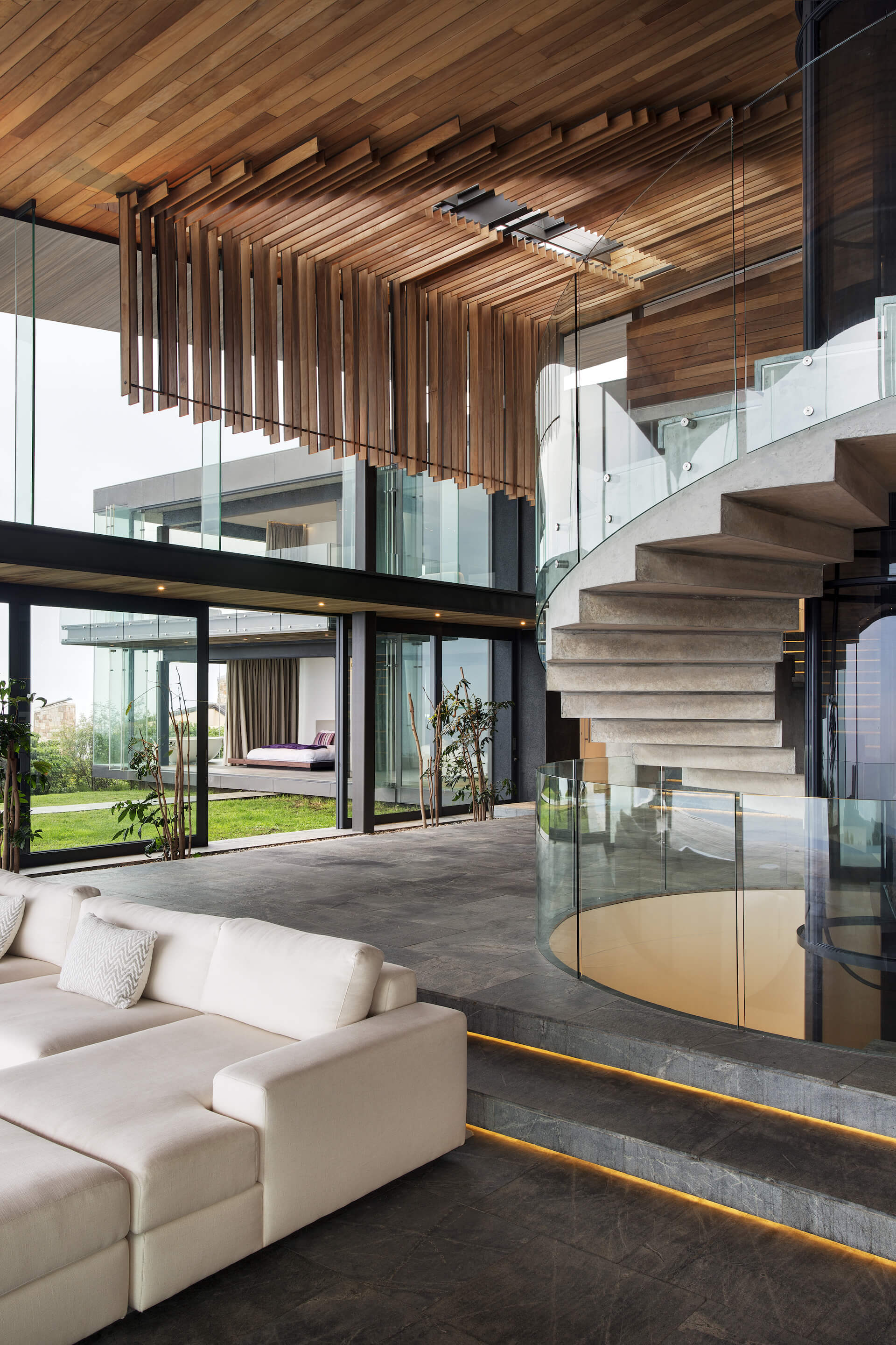 With a vertical, angled view of the central open space, we see the towering views afforded by double height windows, while the stone and glass spiral staircase at right connects the layers. Subtle under-stair lighting glows in lower area.