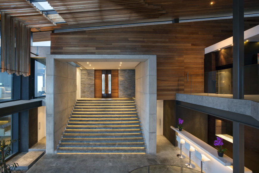 From a raised perspective, we see the glowing steps descending from the main entryway, along with the concrete cubic structure surrounding. The two levels are separated by black I-beams with a glass railing wrapped around the edge.