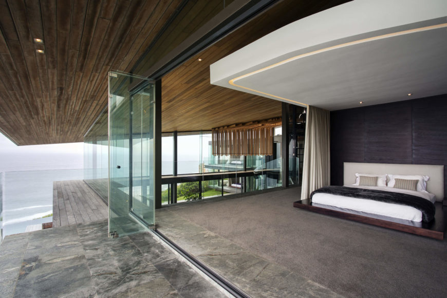 The master bedroom, like every other space in the home, opens onto the balcony via retractible glass panels. A large curtain system, open here, can be drawn for privacy.