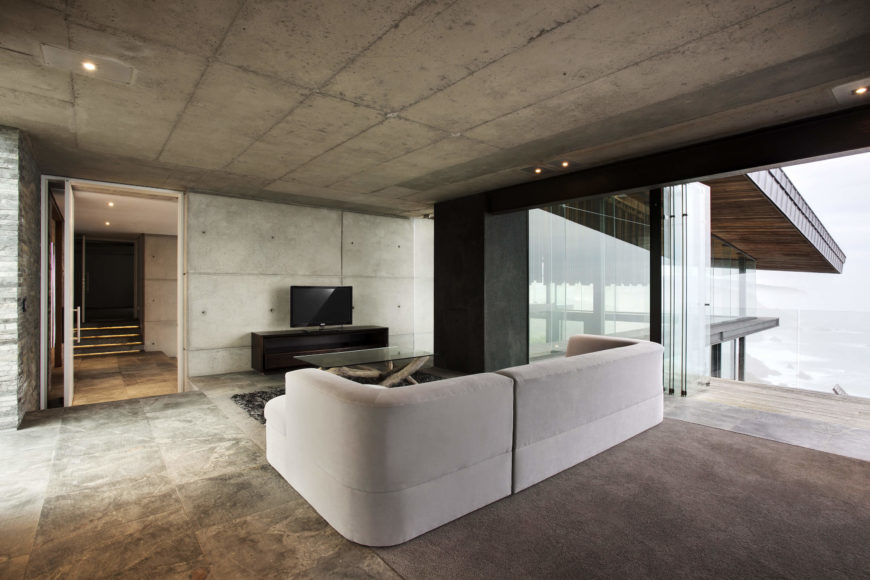 On the upper level, we see a secondary living room space, with beige sectional and glass topped, rustic wood coffee table standing on stone flooring. Full height glass panels retract to blend the space with upper balcony.