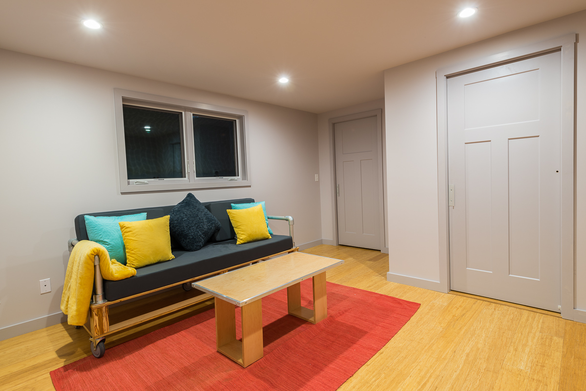 The family room downstairs has the same furniture as upstairs, mixed up with a few new accent colors, including pink, yellow and blue. The lighter hardwood flooring is a departure from the bright flooring on the main level.
