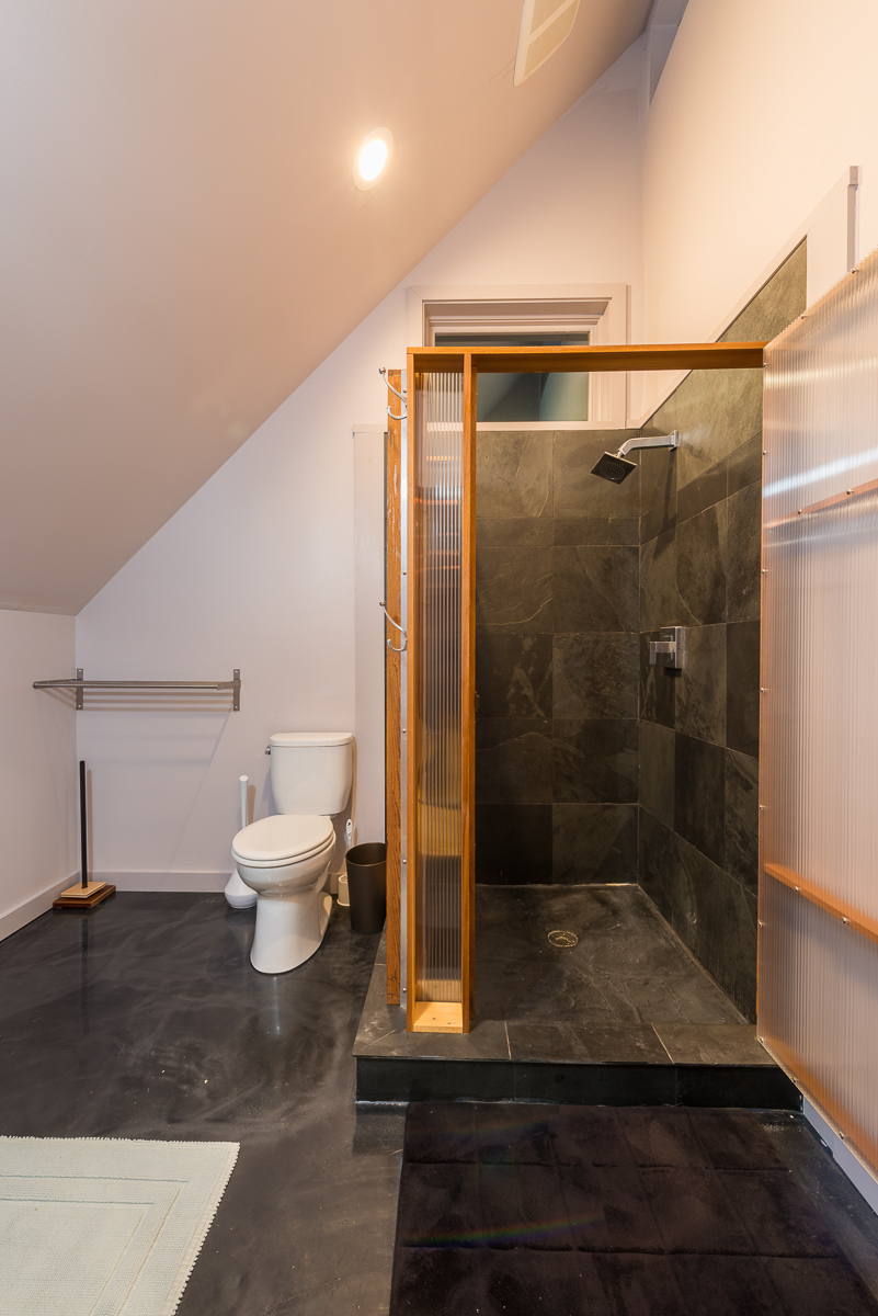 The two bedrooms share a bathroom with a dark tile shower stall with frosted glass and glossy gray flooring.