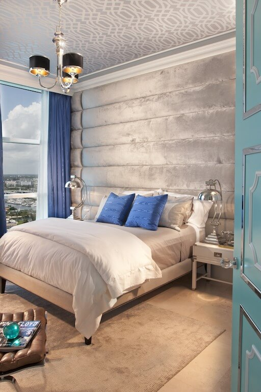 This boy's room is mostly neutral with a bright, traditional blue in the pillows and curtains. The wall behind the bed acts as an accent wall in gray velvet. The ceiling is wallpapered in a subtle geometric pattern.