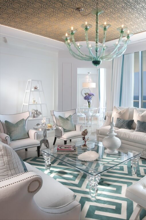 The primarily white living room has a large glass coffee table, and a bright blue and white patterned rug in the main seating area. A large, blue glass chandelier hangs from the wallpapered ceiling.