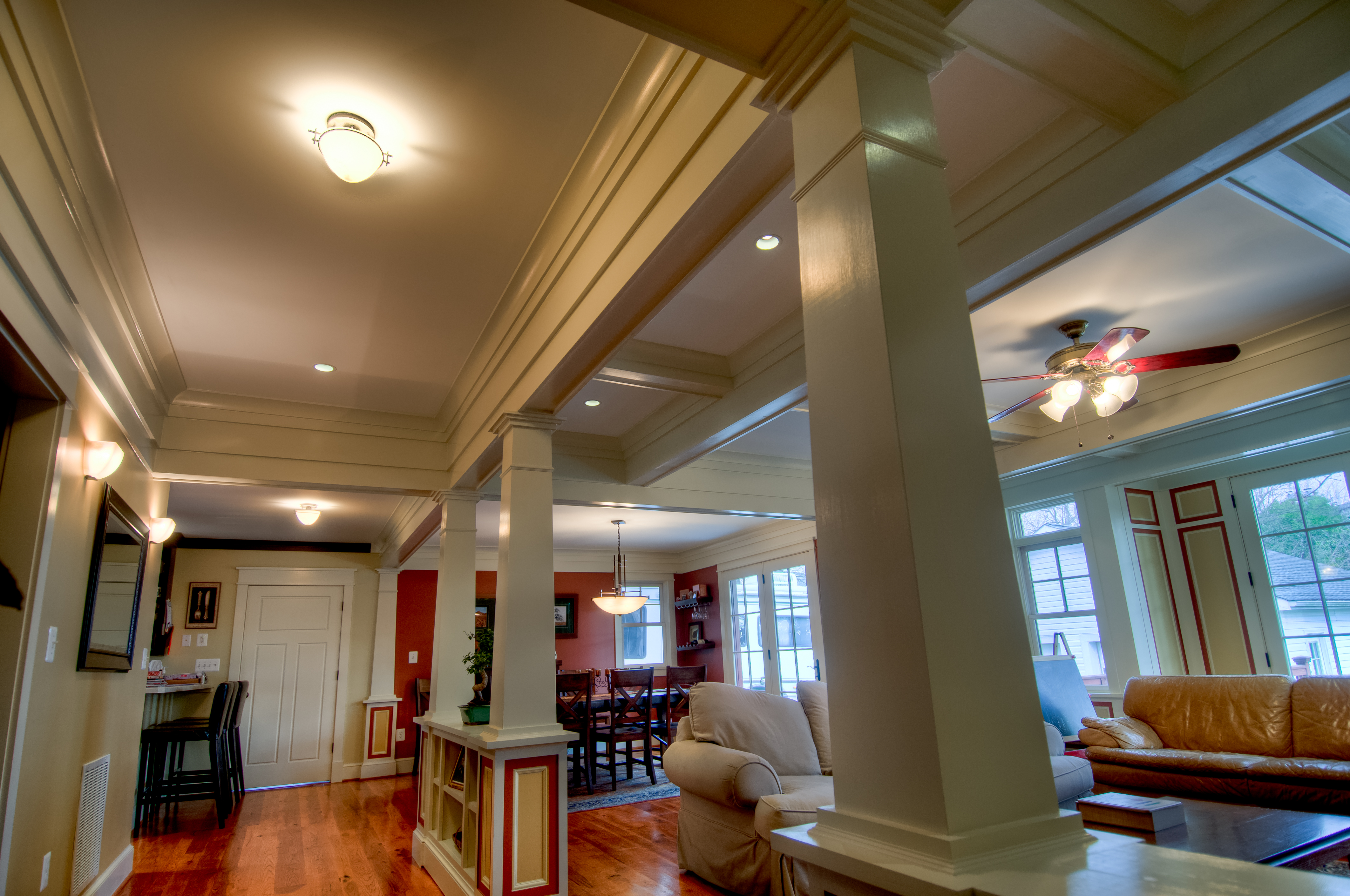 The foyer opens into the living room with a view of the dining room. The living room is divided from the hallway by a series of columns. The tray ceiling of the hallway and the coffered ceiling of the living room further distinguishes the rooms from one another.
