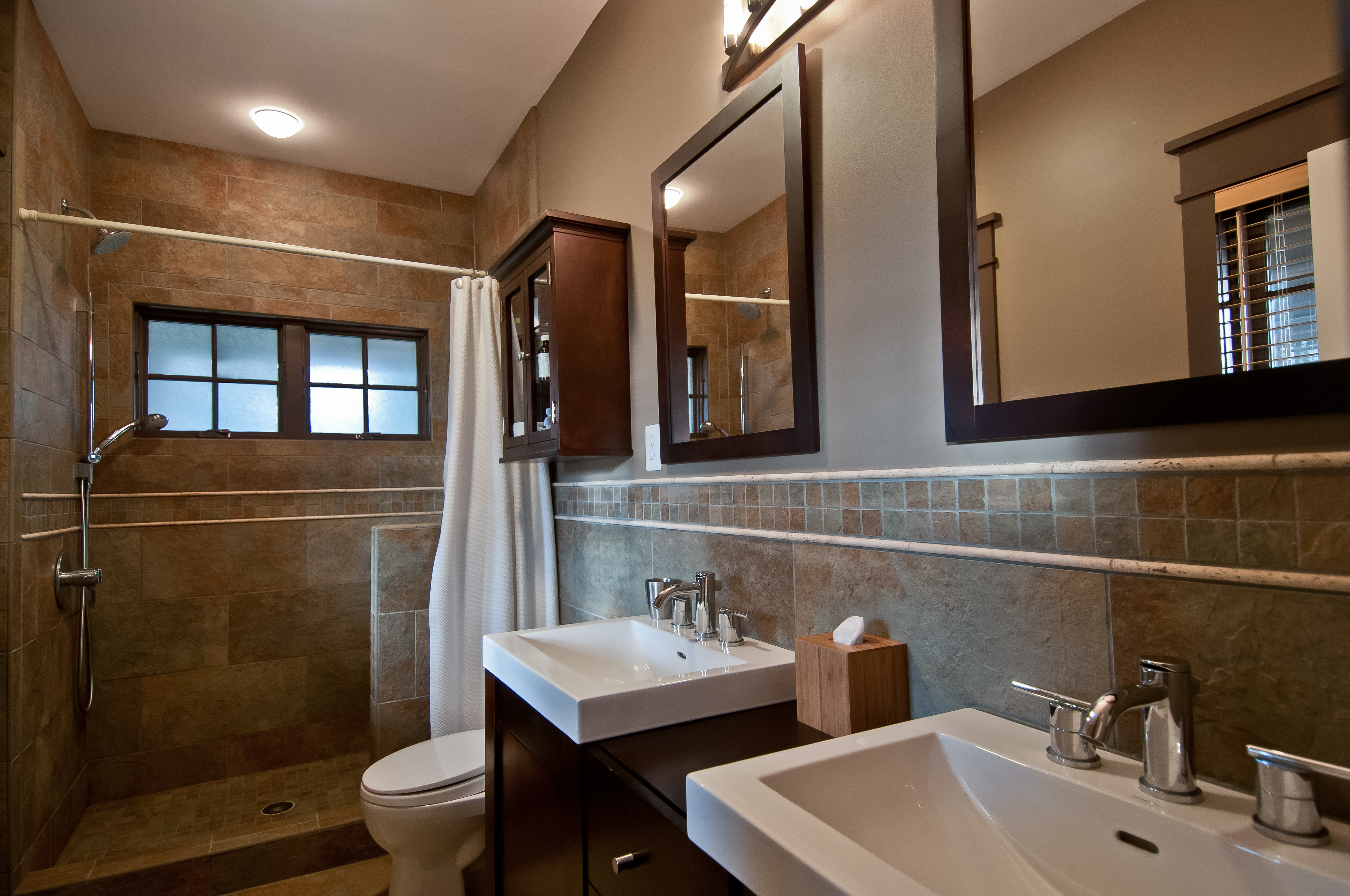 The stone and tile master bathroom has beautiful natural cherry cabinets and an unenclosed shower stall. Chrome fixtures and dual mirrors above the his-and-hers sinks complement the matching medicine cabinet.