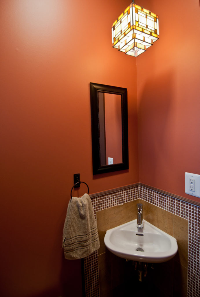 A smaller half-bath on the main level hosts a small corner sink, rich red walls and tile. A colorful light fixture adds life.