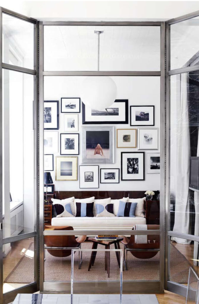 Cozy relaxing space framed in metal and glass features a bold chocolate and white sofa standing across from a pair of leather clad armchairs.