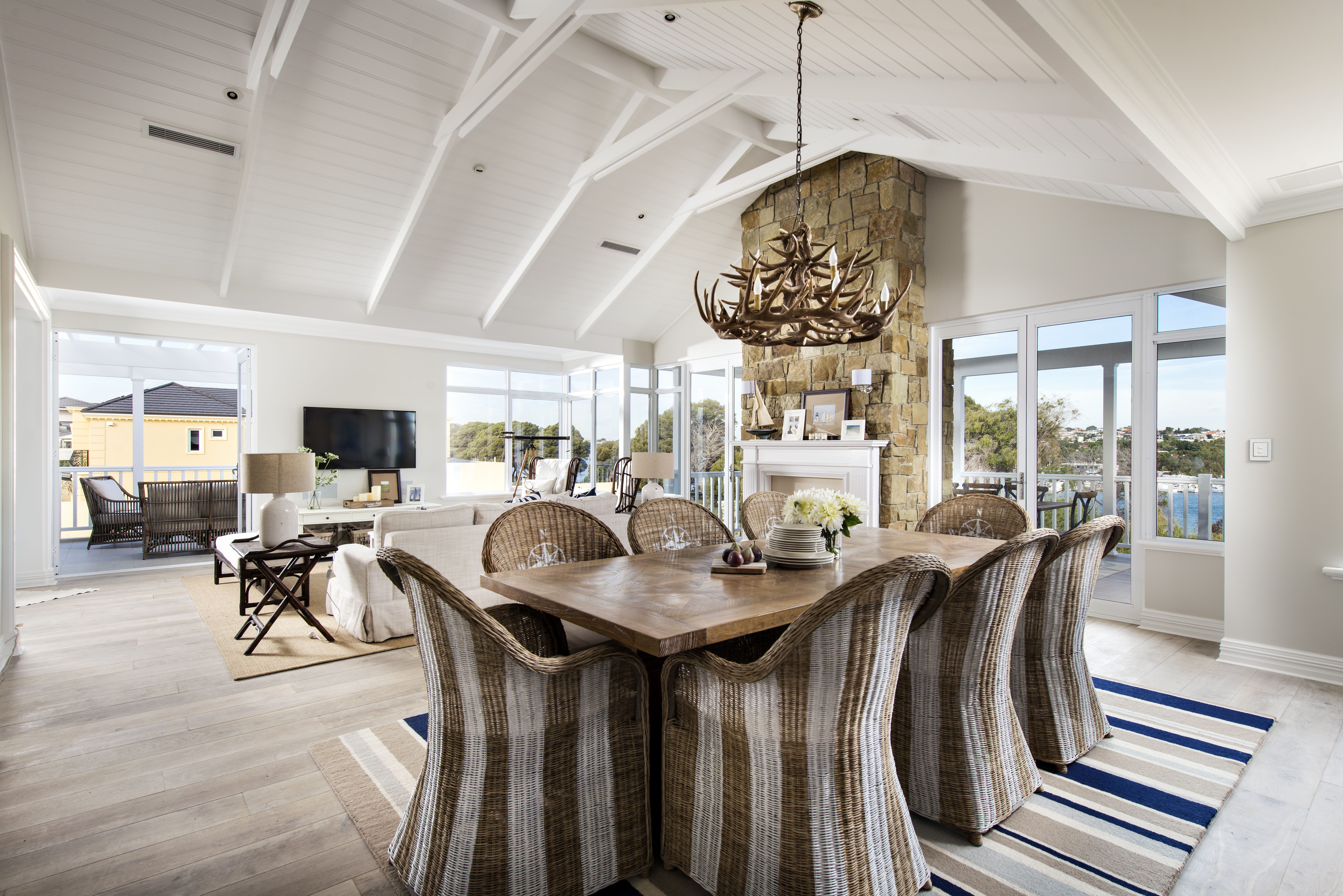 The dining room combines a natural wood table with striped wicker chairs. Each chair has a compass emblazoned on the back of the chair. Blue in the area rug differentiates the space further. An antler light fixture hangs above the dining table.