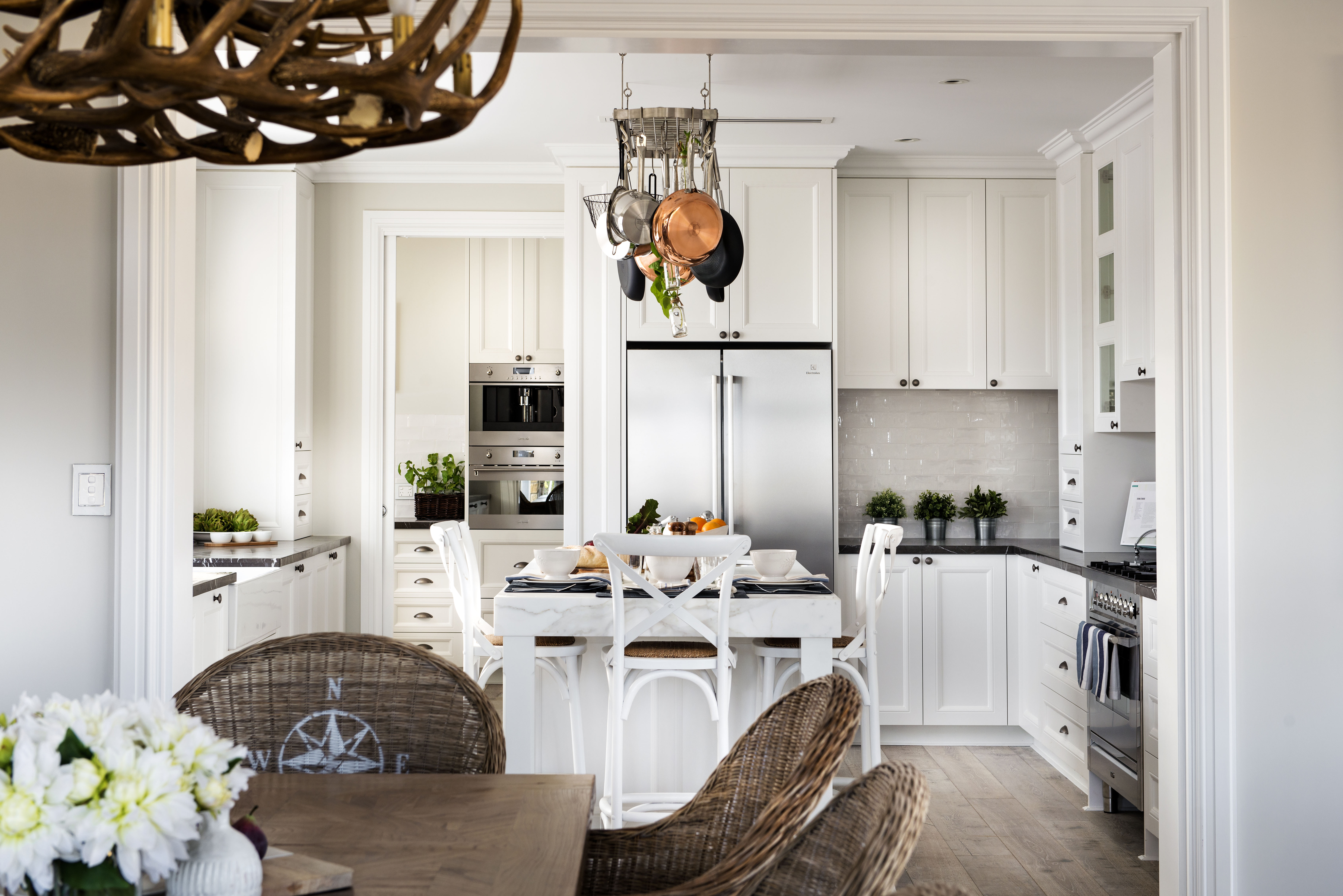 The kitchen is mostly white, with a glossy off-white backsplash. The kitchen is deceptively deep. From this angle, it looks average sized.