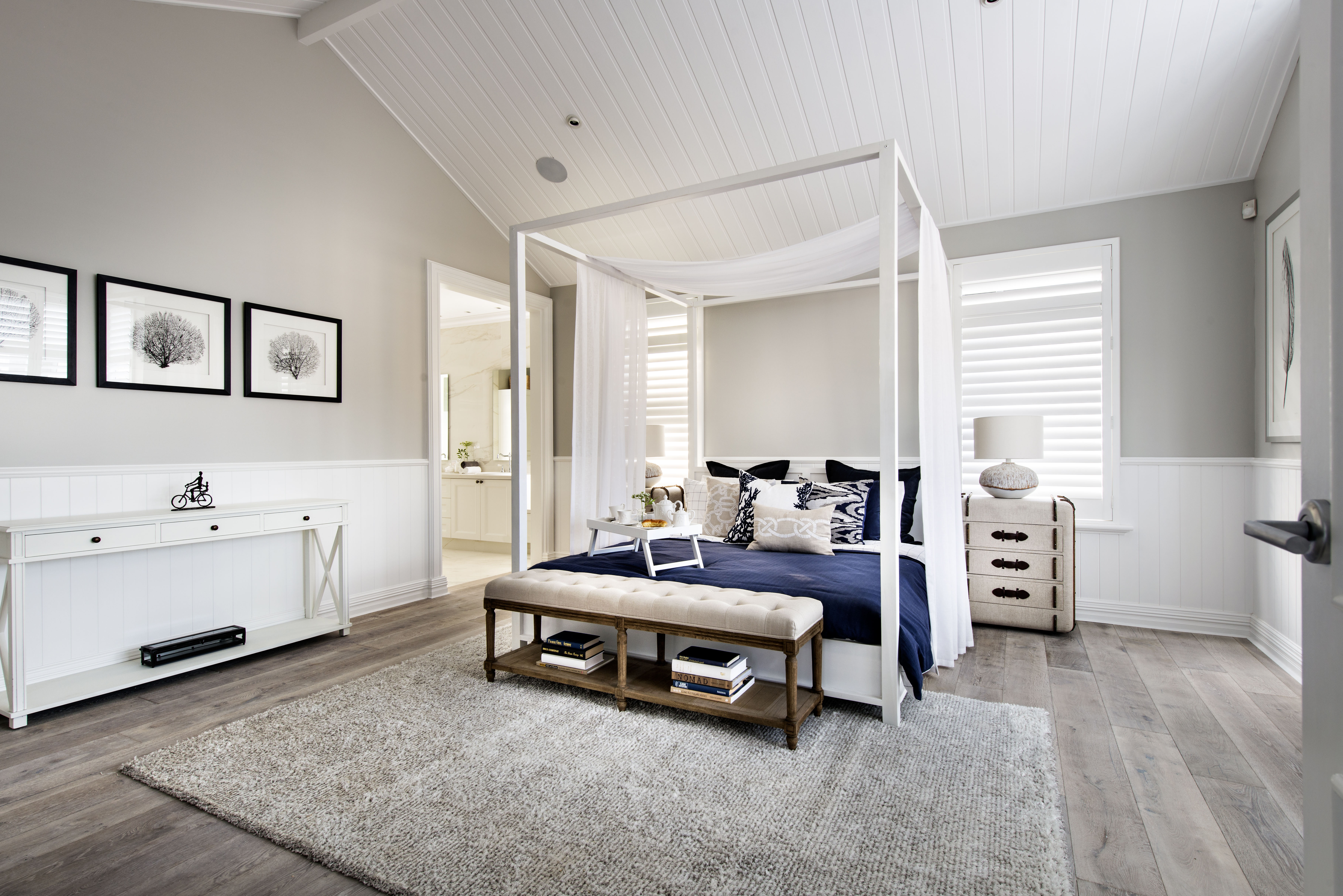 Taking a right off the staircase, the master bedroom suite takes up the back half of the second level. The light gray wood floors continue into this room, unifying the floor. The white walls and wainscoting make another appearance, as does the deep blue from the rug in the dining room.