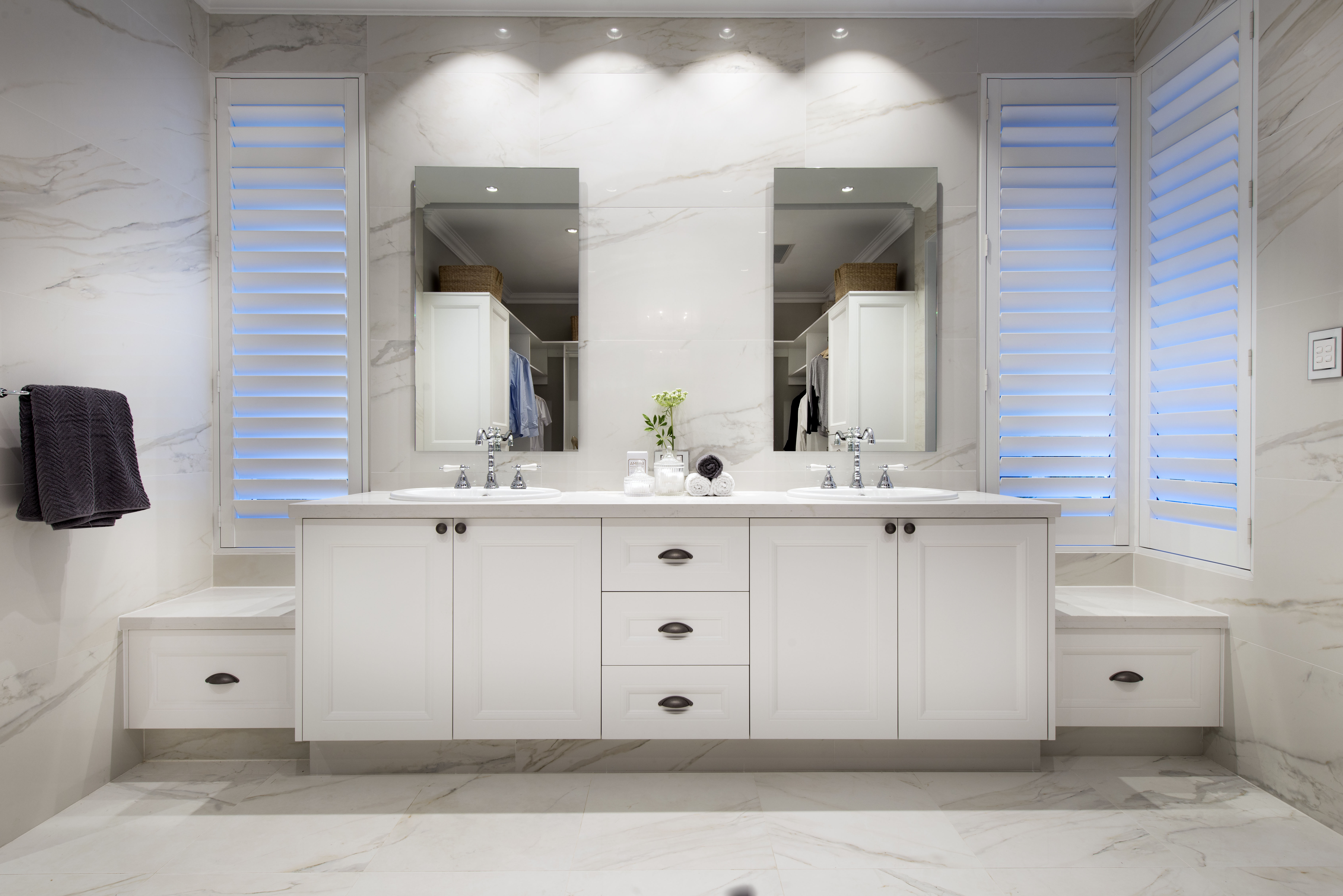 The completely white vanity, paired with the marble flooring, walls and countertops give this bathroom a pristine and luxurious feel.