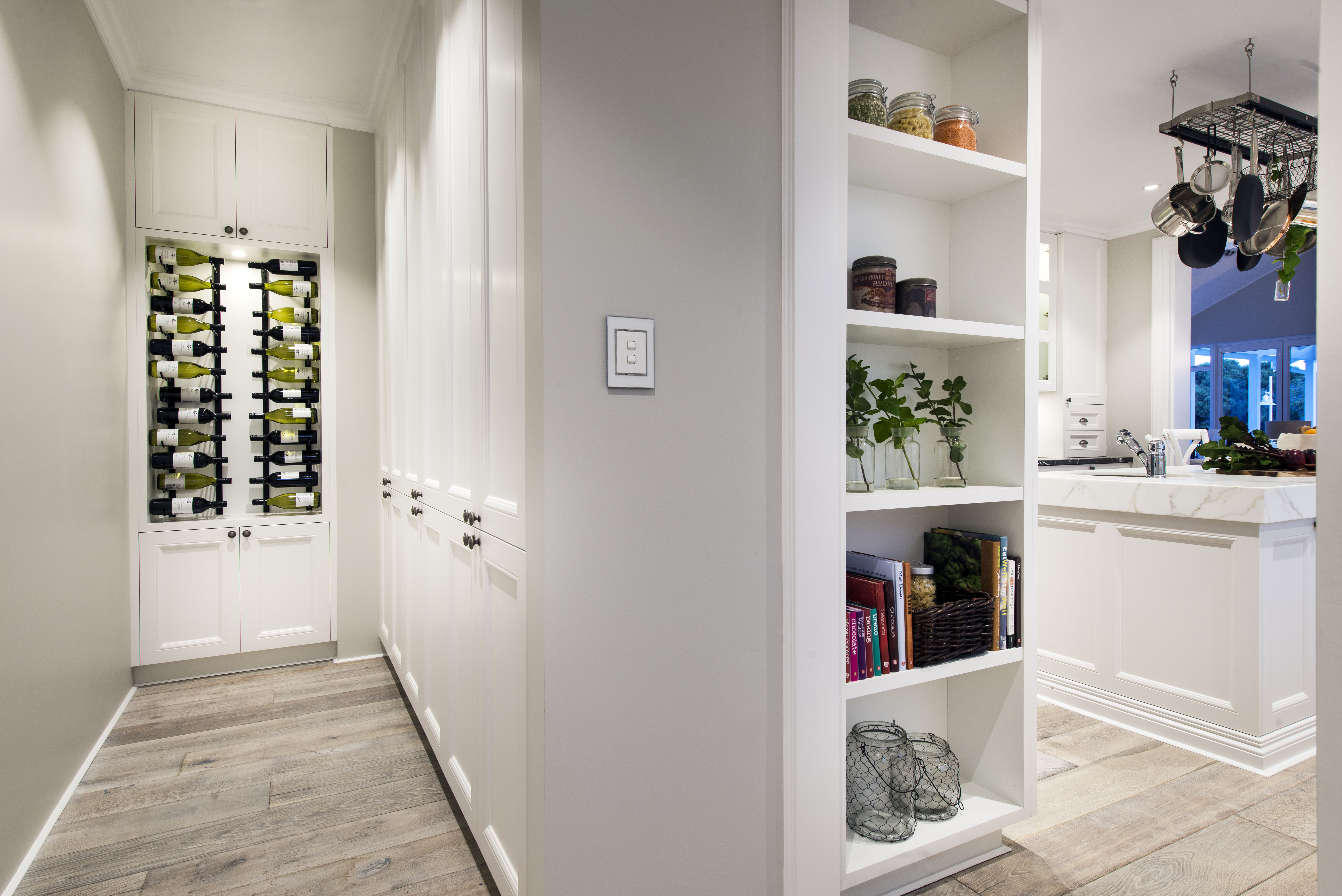 Hidden open shelving can be seen from the pantry, which has twelve cabinets and a wine cabinet as well.