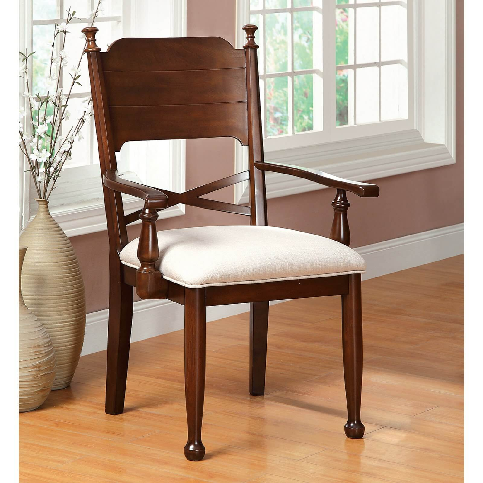 The arm chair features, as one would guess, arms, in addition to the traditional side chair design. Although the frame style can morph the way the arms appear on the chair, the most common design, as pictured here, attaches the arms to the back and seat via narrow pieces.