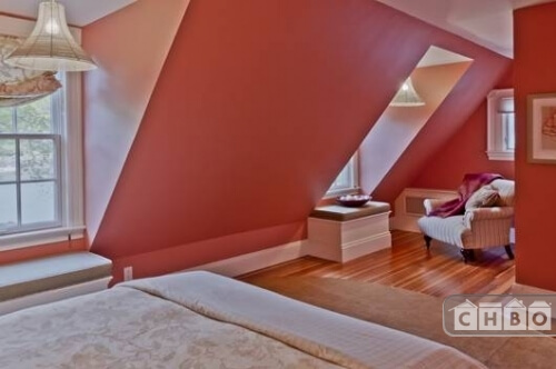 One of the 7 bedrooms is on the third floor. The slanted wall is broken by window seats on the left. The bright red walls and reddish hardwood floor is contrasted by the light floral bedding and accents throughout the room.