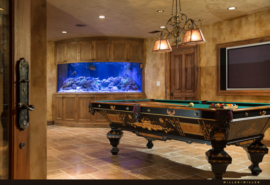 To the left of the billiards table is a large built-in saltwater aquarium with cabinetry above and below.