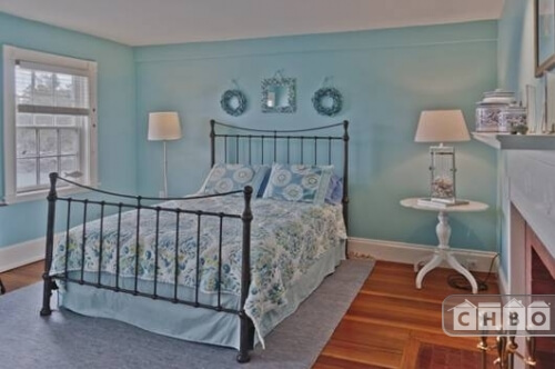 This next bedroom is vastly different from the previous one. In pale Tiffany blue and bright floral bedding, the iron bed frame contrasts with the white furniture, trim and fireplace mantle.