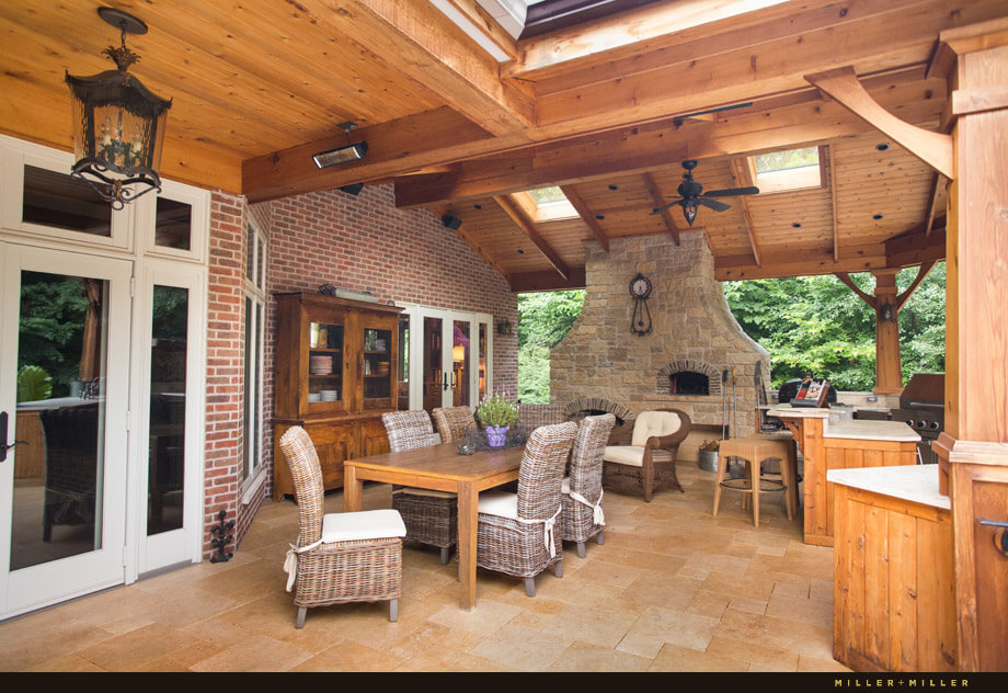 The large backyard is resort style. Immediately outside of the doors is an entertaining area with a dining table, wicker chairs and a cooking area.