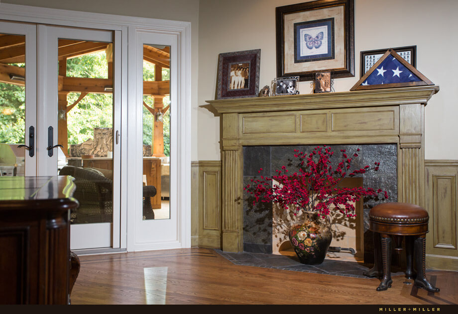 A closer look at the fireplace reveals that it is currently not in use. A bright red flower arrangement sits in front to brighten the space.