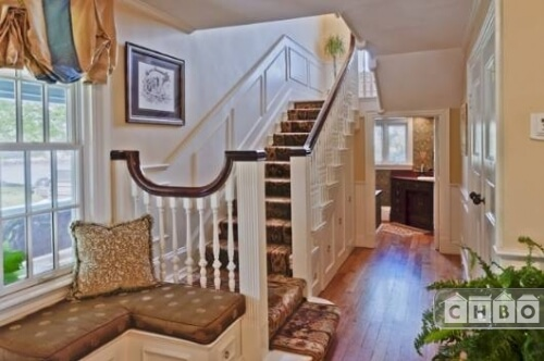 The entryway to the home has a small mudroom bench near the window and leads directly into a bathroom. To the left is a carpeted staircase leading to the second floor. More main level rooms are off the hallway to the right.