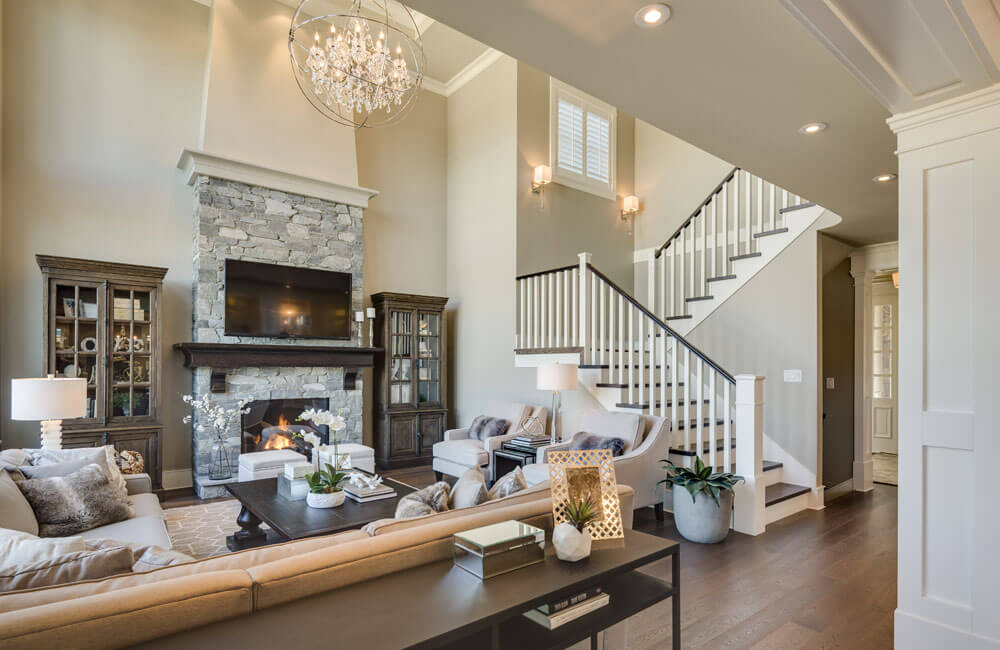 The view from the edge of the dining room shows the hardwood staircase leading upstairs and the foyer. The crystal orb chandelier adds a modern twist to the traditional chandelier.