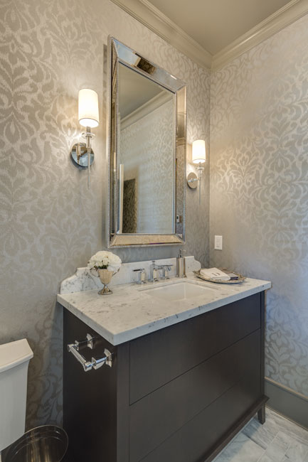 A small half-bath downstairs is dressed up with chic wallpaper and sleek dark wood vanity.