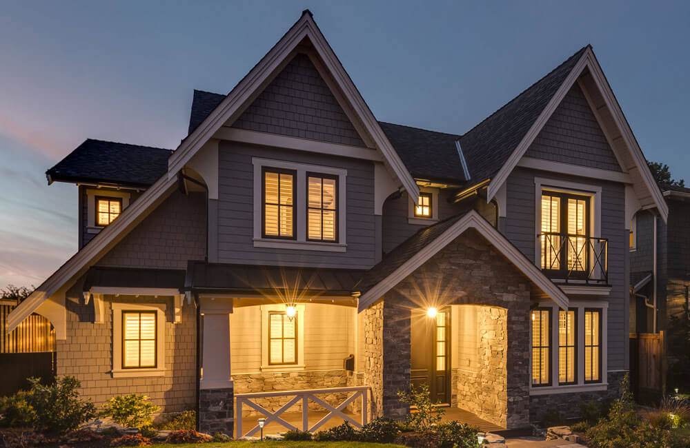 A nighttime view of the front entryway to the home, showcasing the simple and elegant landscaping.