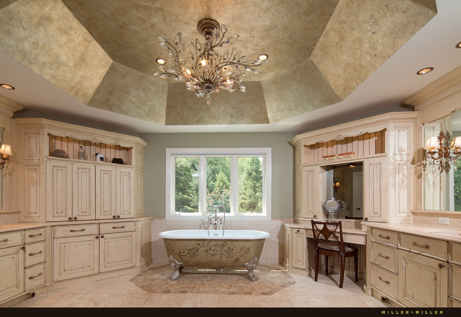 The adjoining master bathroom has a gorgeous crystal chandelier hanging from the vaulted ceiling. Around the perimeter of the room are built-in cabinets, vanities, makeup tables and towel storage.