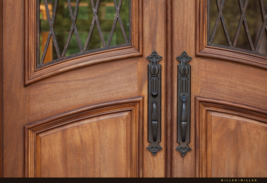 The entry door to the home is solid mahogany with iron handles.