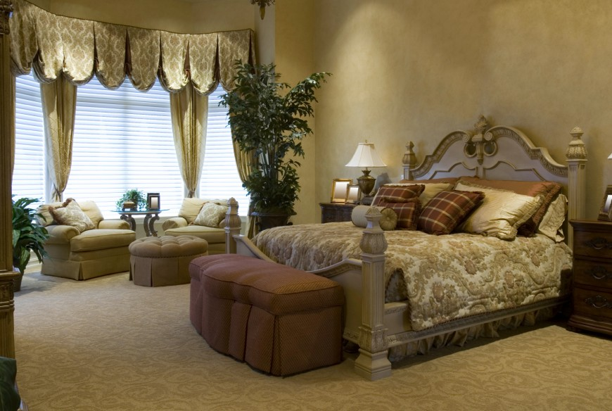 Comfort is the key element of this master bedroom, with the majority of the furniture being soft, plush armchairs and ottomans. The bed is of grand design, with an ornately carved bed frame.