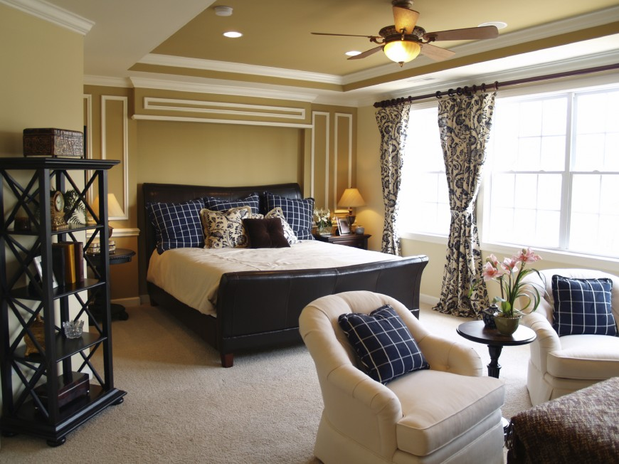 This contemporary bedroom has a leather sleigh bed, dark furniture including nightstand, side table and shelving, and a small seating arrangement with matching pillows. Wainscoting on the walls behind the bed make an accent wall.