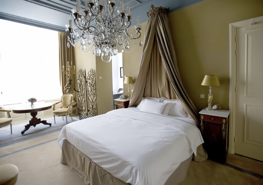 A beautiful and elegant master bedroom with a crystal chandelier, a sculpture topped with a candelabra, and bed curtain in place of a headboard.