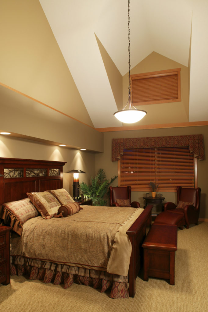 This traditional style master bedroom has two ultra-comfy inviting leather recliners in a small seating arrangement near the window. The ceiling has an unique architecture with one high shaded skylight.
