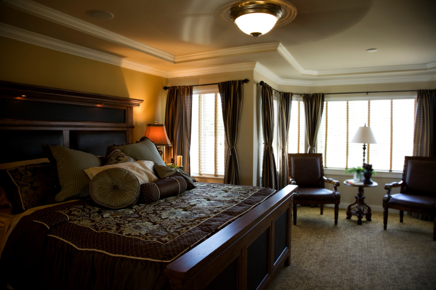 Two layers of crown molding give the illusion of a tray ceiling. The rich, dark bedding and curtains perfectly complement the dark natural wood furniture.