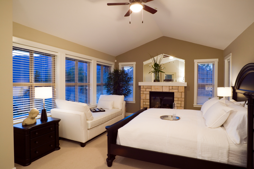 A wall lined with windows has shorter furniture in front of it to take advantage of the space. On the far wall, a masonry fireplace is topped with a mirror that matches the angle of the roof.