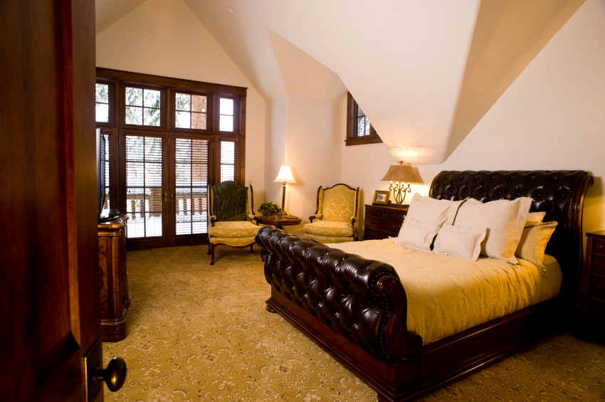 A quilted leather sleigh bed and large rich wood furniture rest on top of a subtly patterned carpet. The room has an unique architecture.