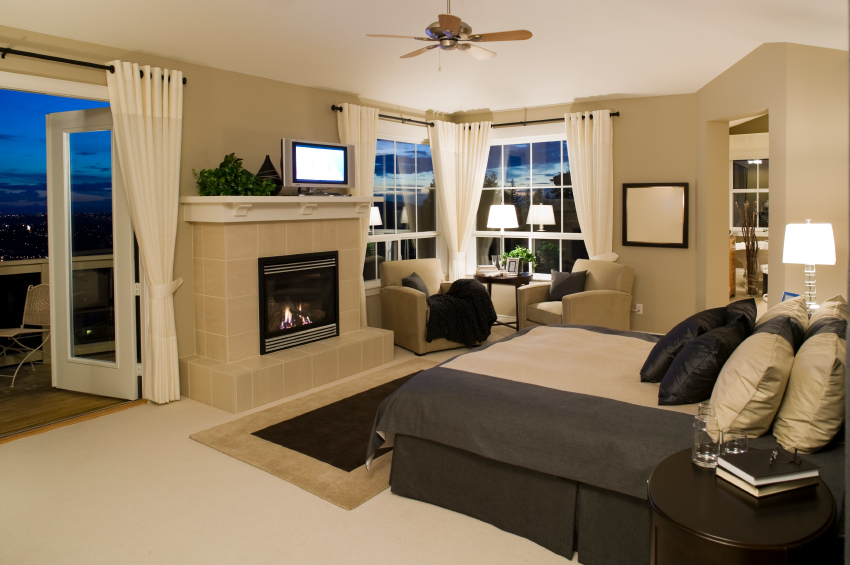 This contemporary bedroom has both an enclosed fireplace and doors that open up to a balcony with a great view.