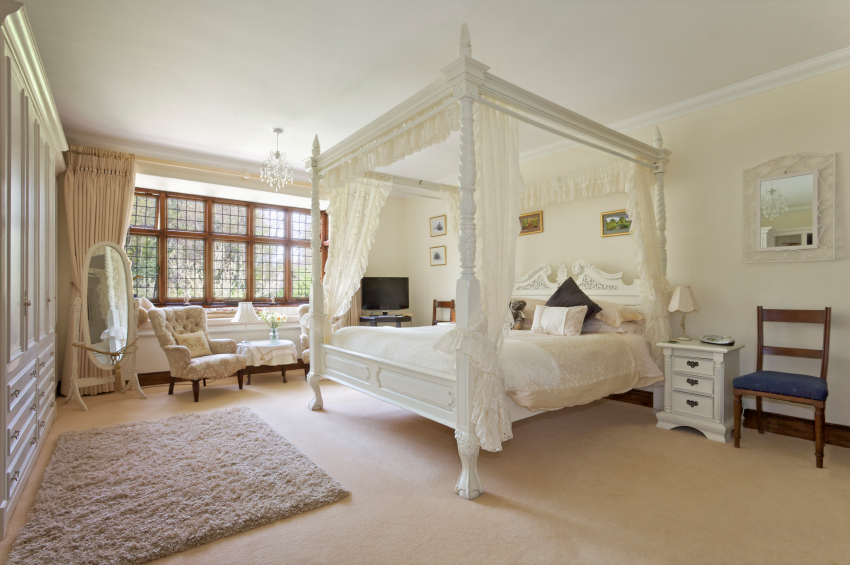 Delicate and airy curtains hang from the carved white four post bed. A small chandelier hangs above the windowed seating area. An expansive wardrobe covers one whole wall.