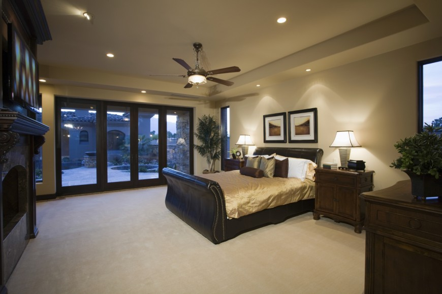 The focal point of this bedroom is the leather sleigh bed. On the left side of the room stands a large, ornate fireplace. Sliding glass doors lead out to a courtyard.