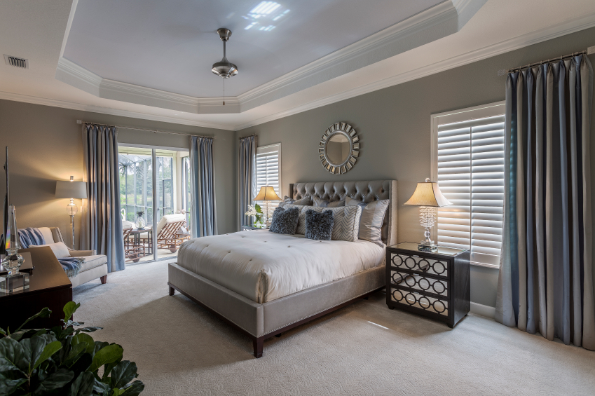 This Neutral Bedroom Is Dressed Up With Blue Accent Pillows And Curtains A Sliding Glass