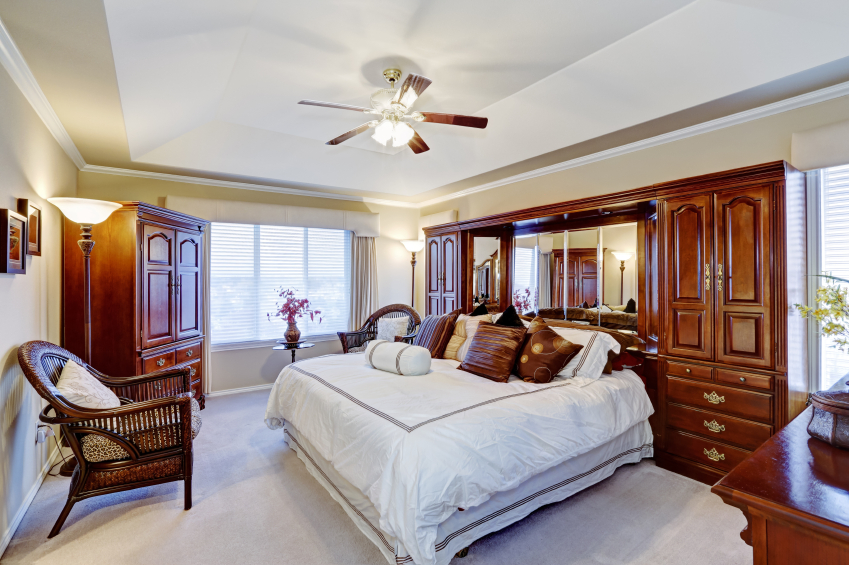 A contemporary white and natural wood bedroom with a tray ceiling. Built in wardrobes are on either side of the bed.