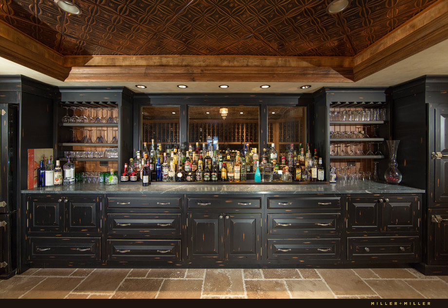 A view from behind the bar shows the wine cellar just behind the window. The black cabinets are distressed.