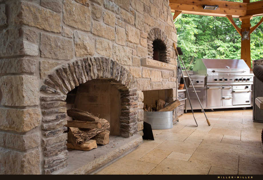 The stone wood-burning fireplace also has a pizza oven just above and to the right.