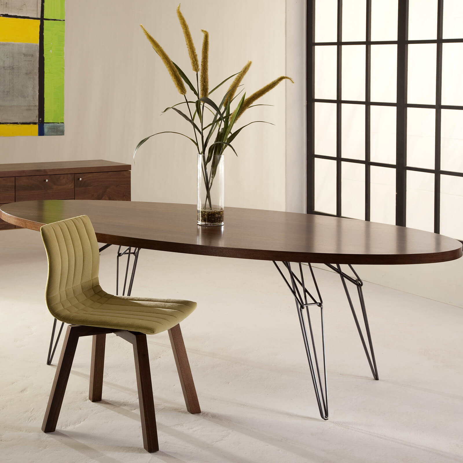 Our second oval table example is a modern minimalist design, with a narrow, long body over wire frame legs.