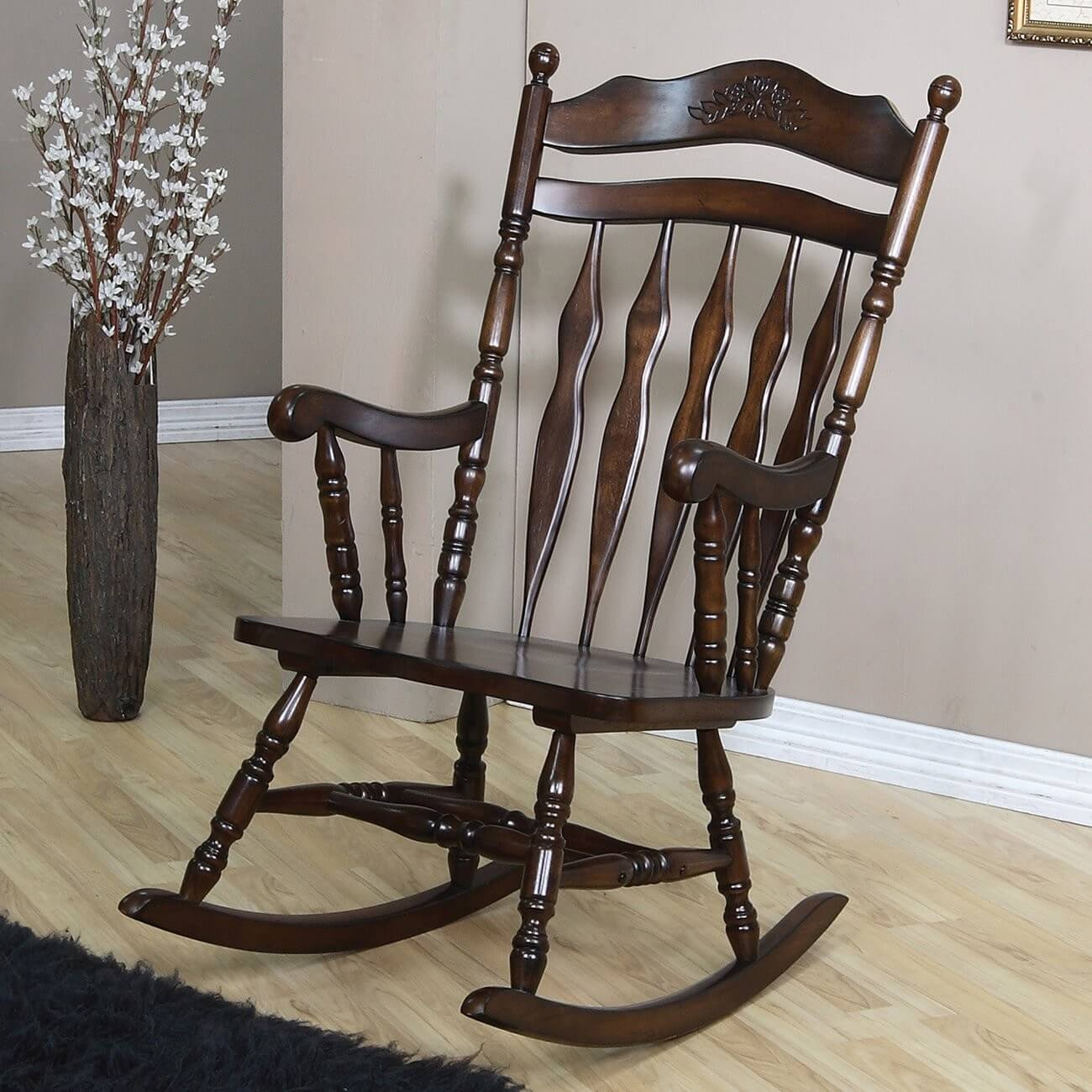 Traditional rocking chairs feature a solid wooden frame with arms and carved detail. Our example boasts a filigreed carving in the main back piece.