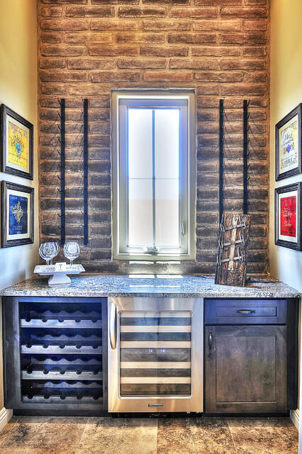 This home bar area with distressed dark wood cabinets has a miniature refrigerator and wine racks. An Adobe Brick veneer accent wall behind the bar adds style and rustic flair to this little alcove.